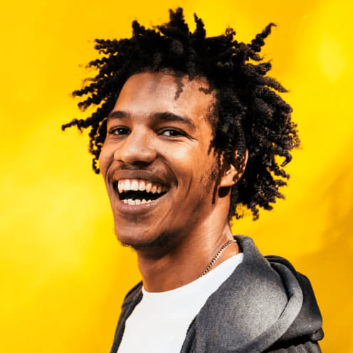 Man smiling at picture in front of a yellow background