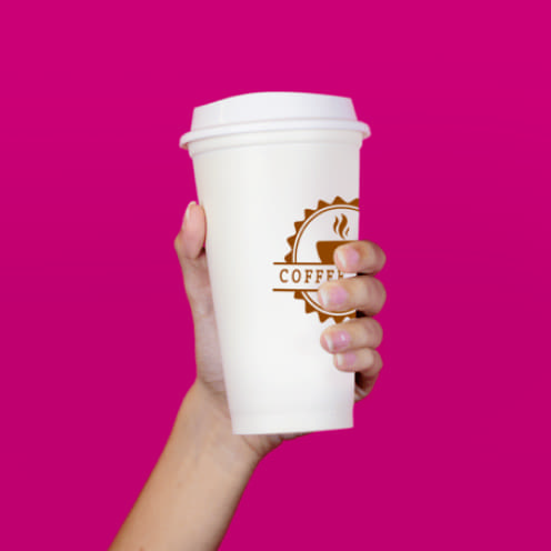 One hand holds a coffee cup in front of a pink background