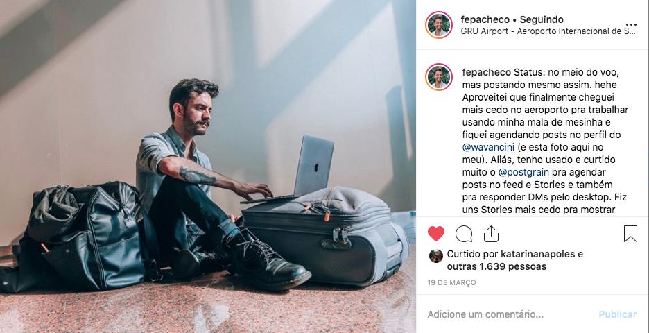 Captura de tela de foto publicada por Felipe Pacheco. Sentando no chão de aeroporto, usa o notebook.