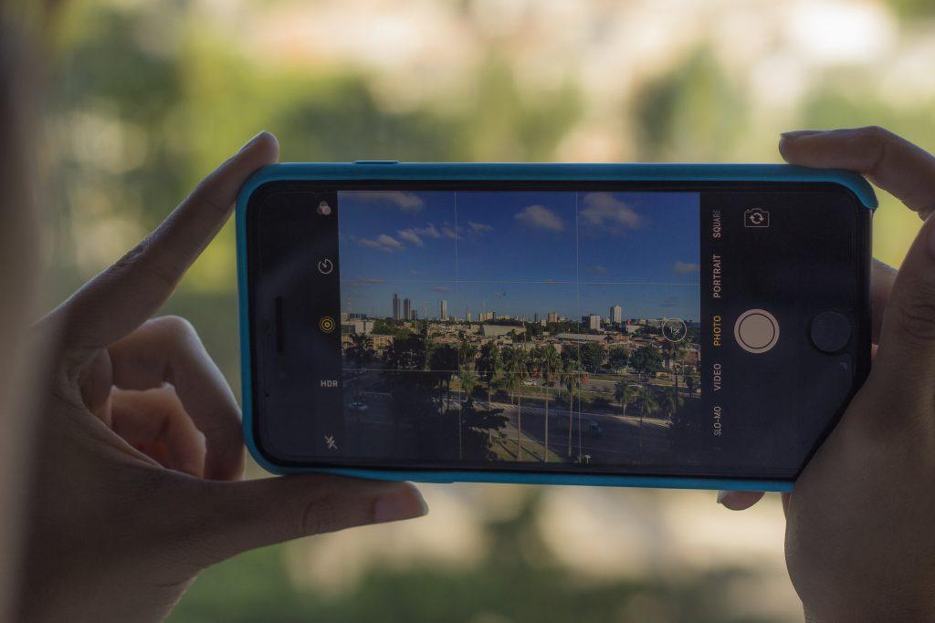 Mãos de uma mulher seguram um iPhone 7 Plus na cor preta enquanto fotografa a cidade através de uma janela. Pela tela do celular, que está com a grade ativada, é possível ver prédios, uma avenida onde carros trafegam, árvores e um céu azul com nuvens.