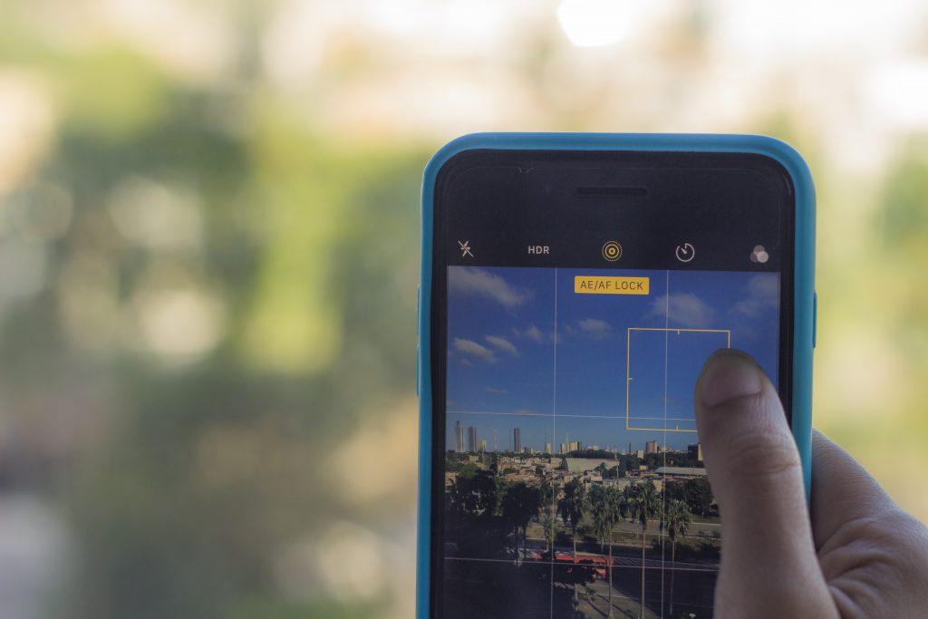 Foto de um iPhone 7 Plus em evidência, com o fundo desfocado. O dedo na tela controla a exposição da fotografia.