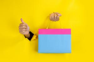 Mãos furando uma parede de papelão amarelo. Uma segura uma sacola de compras e a outra faz o símbolo de legal