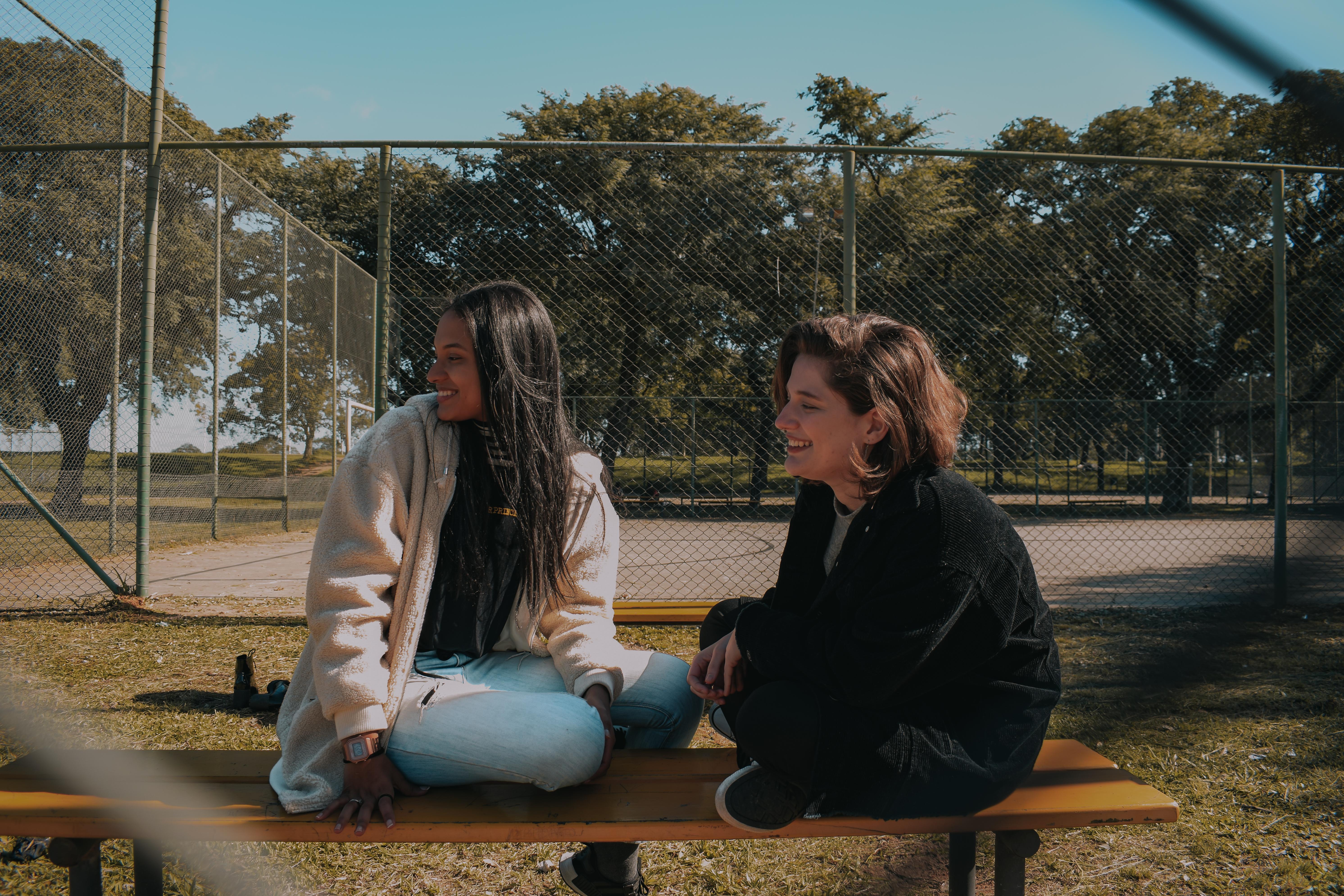 Mulheres LGBTs riem sentadas num banco de um parque