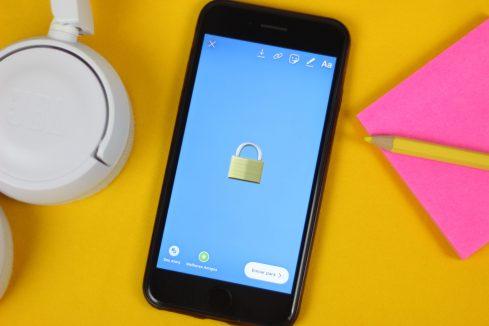 Celular aberto em uma imagem com um cadeado em cima de uma mesa amarela